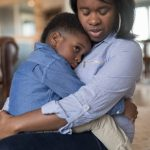A cute preschool-age African American boy hugs his mom tight while they sit on the floor in the living room. They both have serious expressions.